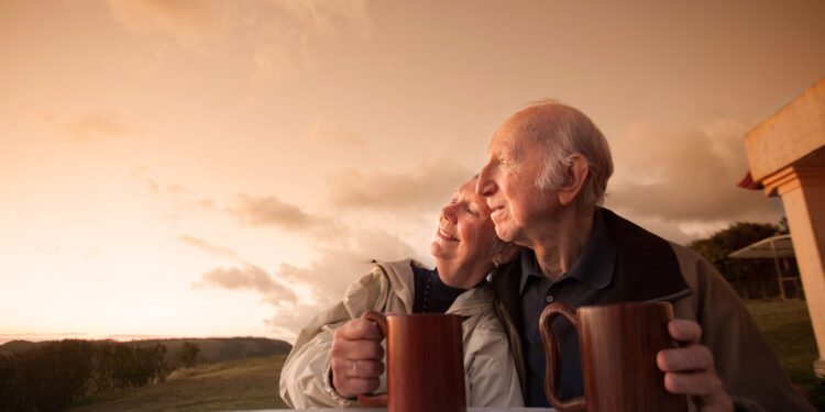 An old couple sit arm in arm outside looking at the sunrise.