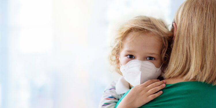 Child with respirator on mother's arm.