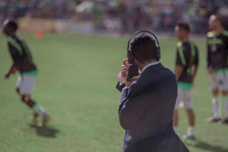 Reporter mit Mikrofon am Rand eines Spielfeldes