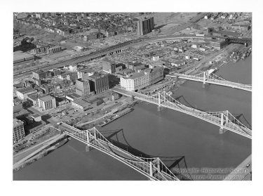 """Aerial view of the North Side, featuring Pittsburgh's """"Three Sister"""" Bridges, the Sixth, Seventh, and Ninth Street Bridges, Allegheny Conference on Community Development Photographs, Detre Library & Archives at the History Center"""