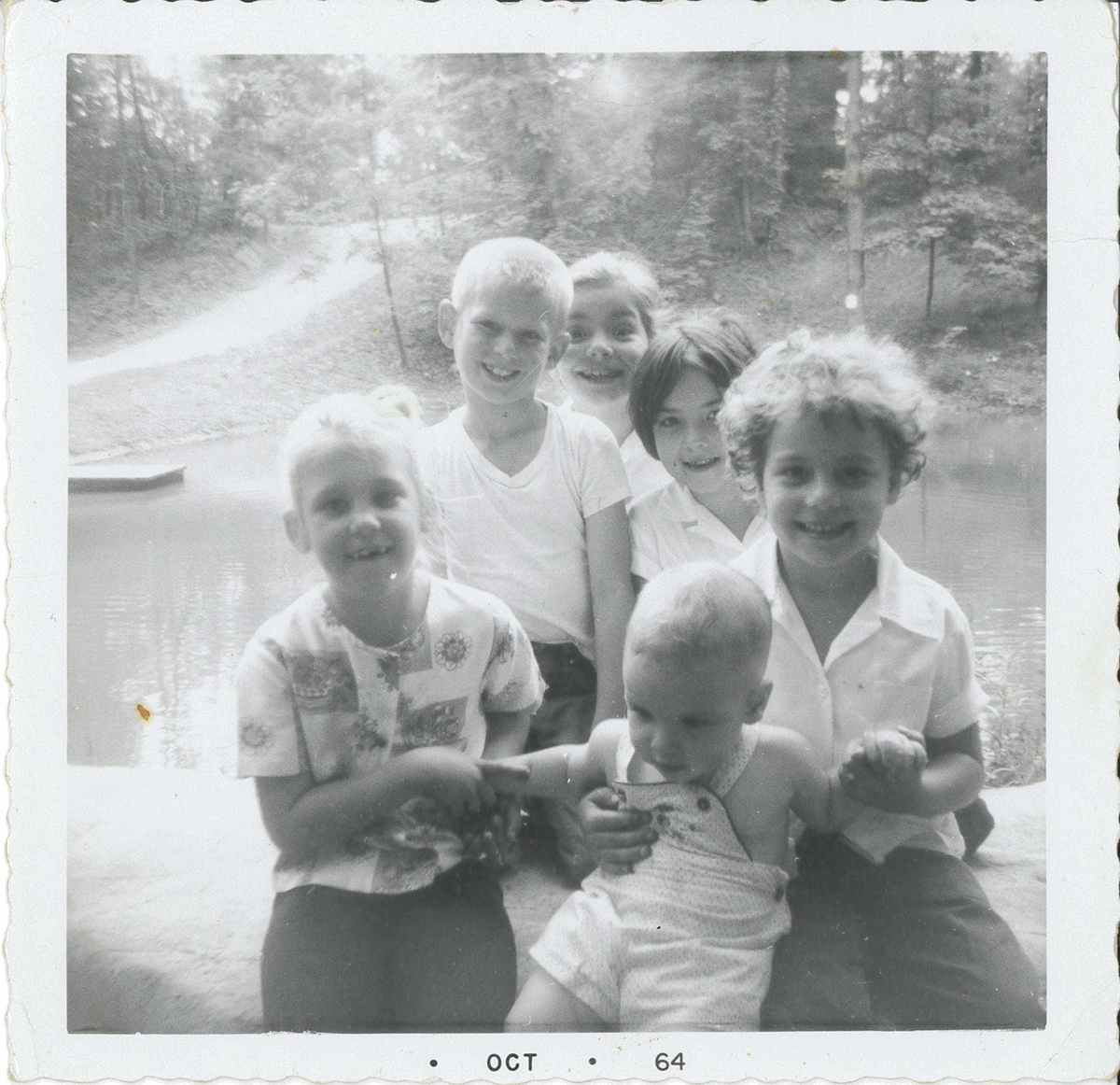 """From the back of the photograph: """"Taken the last day of school June – 64. Terri and Barry Andrews. Patience, Francie, Erin(?) and Danny at the Pond on Miller Property later Meadowcroft Village."""" The blacksmith shop, still there today, would be finished that July on the hill directly across the pond."""