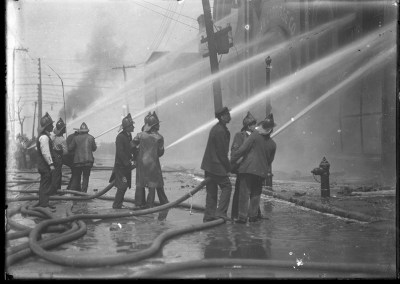 A group of firemen using hoses to put out a fire at the Gerber Carriage Co. in downtown Pittsburgh, 1904.