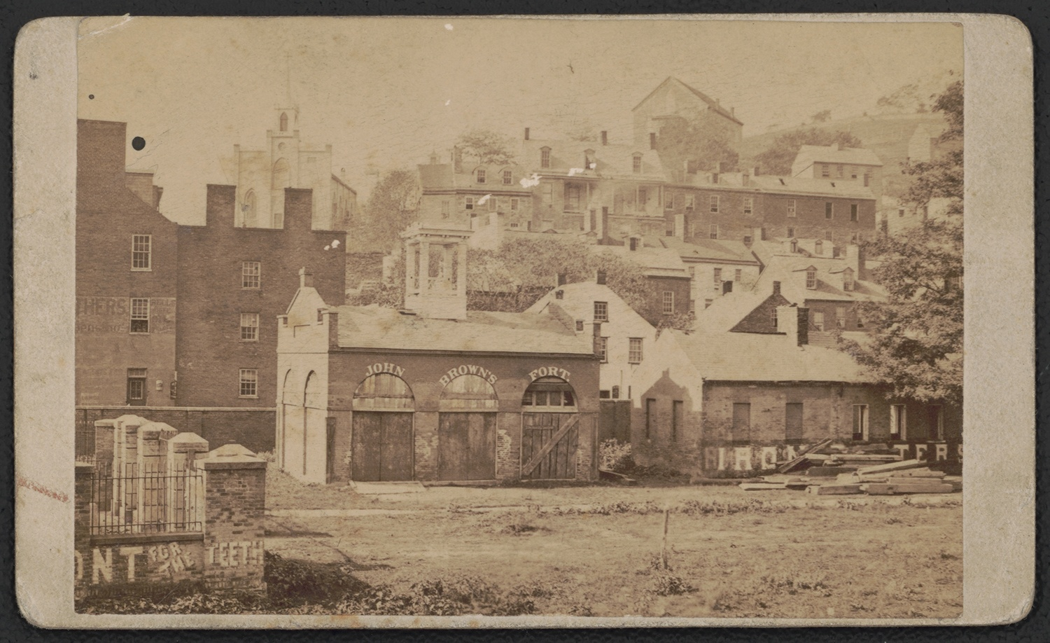"""Photograph showing the fire engine house used by John Brown during his raid on Harper's Ferry, c. 1885. The words """"John Brown's Fort"""" were painted on the building to attract tourists. Courtesy of the Library of Congress, Prints and Photographs Division."""