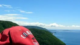 Küste Cape Bretons, davor Rote Kappe mit Aufschrift Canada est. 1867