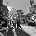 ©Ken Shung - Bubble Boy at The Fair, NYC. Black and white, small boy in a stroller, playing with bubbles from a bubble gun