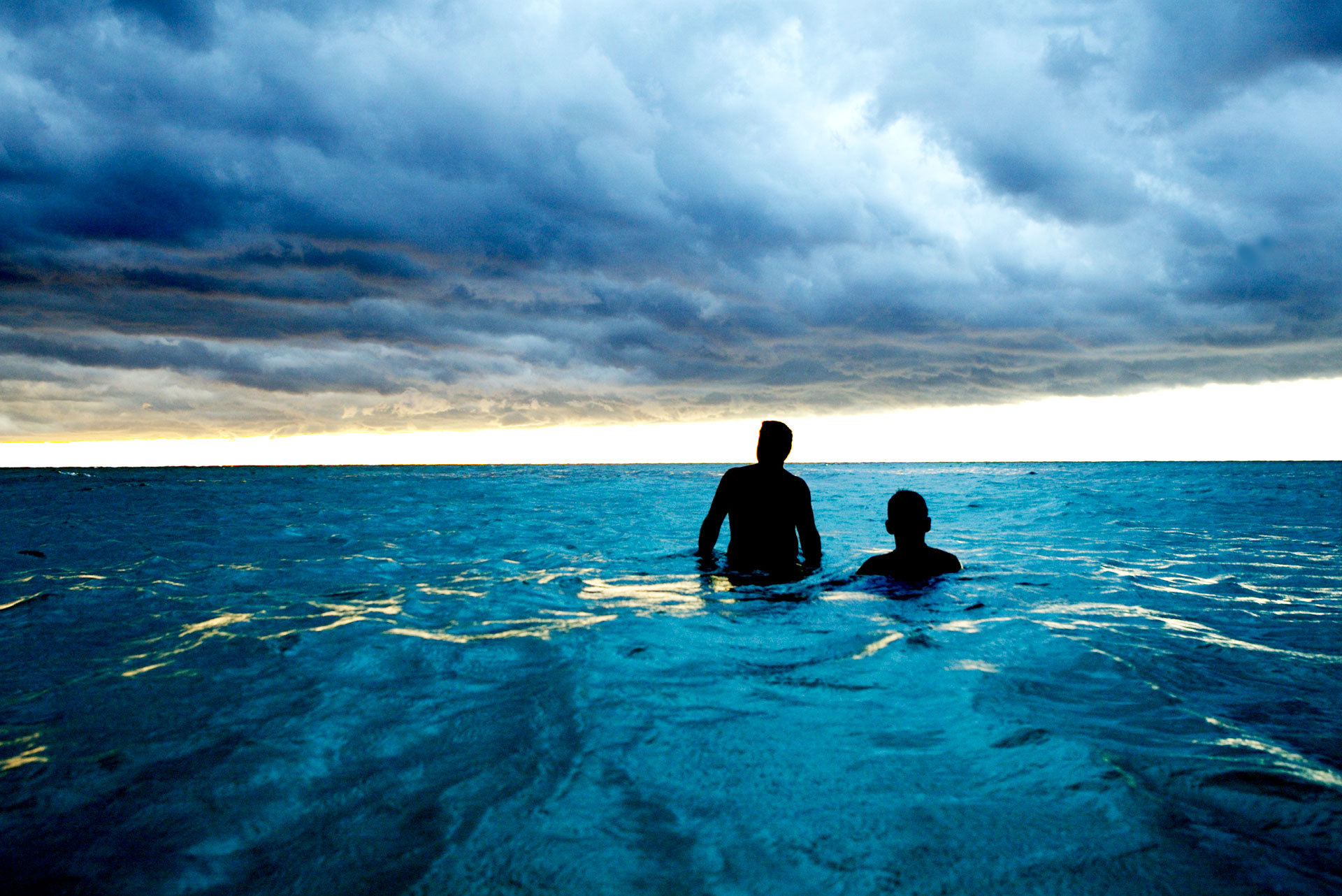 Jason Florio photography - color image of two Cuban men wading in a vivid blue sea, silhouetted against a stormy cloudy sky overhead, Cuba
