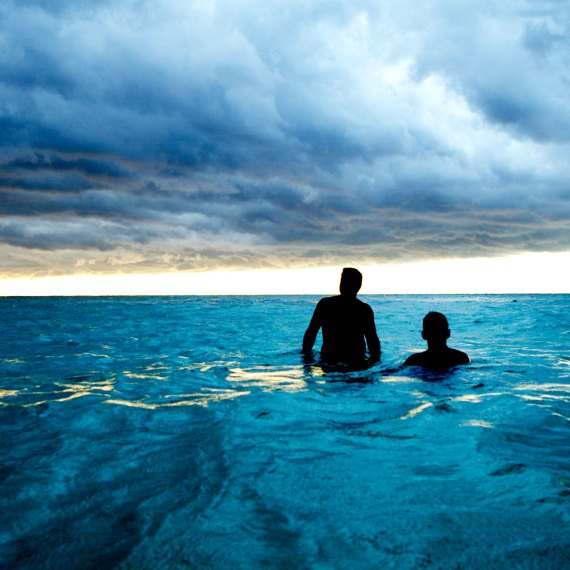 ©Jason Florio 'Sea & Clouds Cuba' . Color - two men wading in the blue sea, with cloudy skies overhead