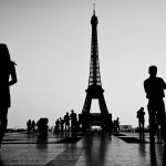 ©Ken Shung - Paris, Eiffel Tower. Black and white- people standing in front of tower, silhouetted against the sky