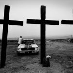 ©Robert Goldstein '3 Crosses, CA'. Black and white - 3 wooden crosses in a field & Mustang car, Bakersfield, USA.