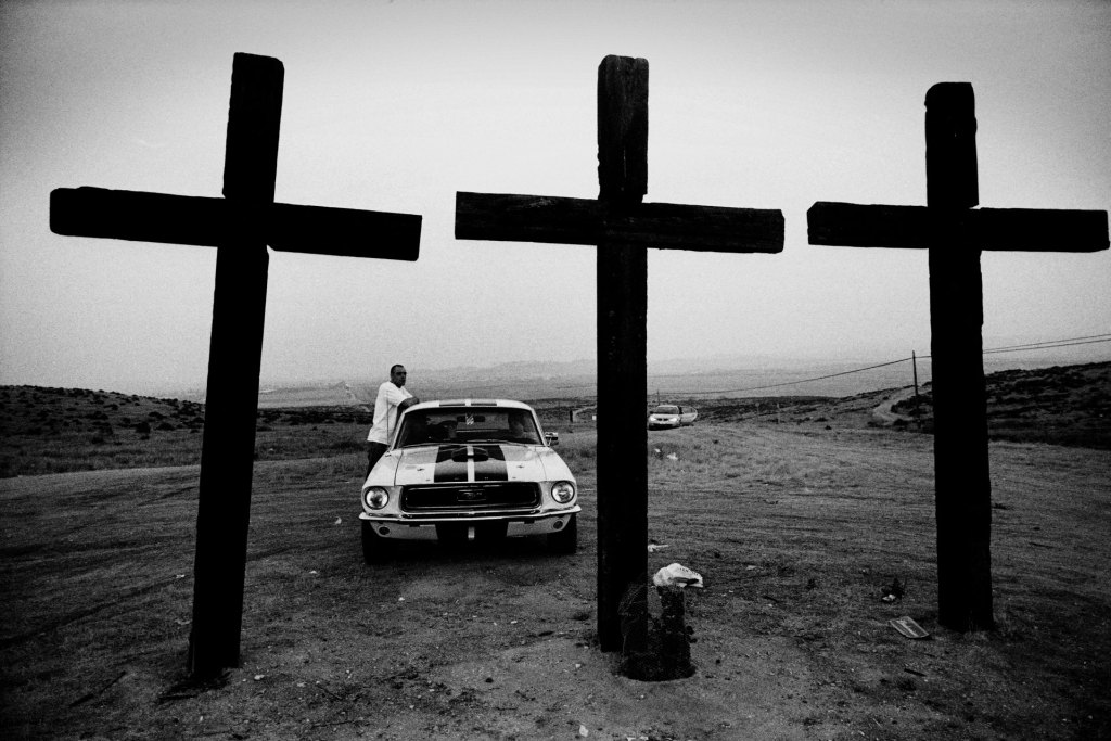 Robert Goldstein Photography - image of a man standing by his car, with 3 giant Crosses in the foreground, Bakersfield, CA