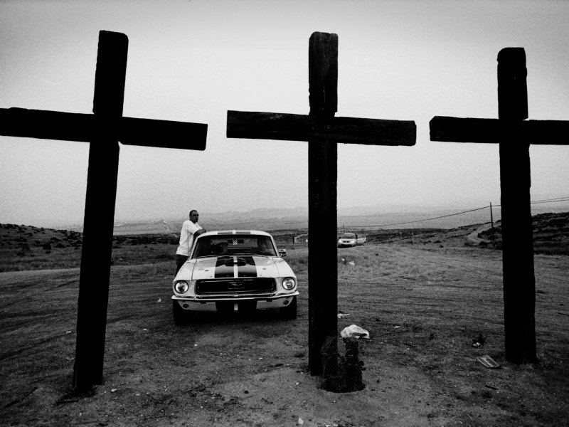 Robert Goldstein photography - black and white image of a Man standing by his Mustang car, with 3 large wooden crosses in the foreground, Bakersfield, CA