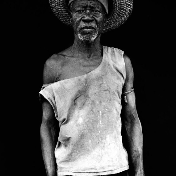 ©Jason Florio - The Farmer, The Gambia, West Africa. BW portrait from Makasutu series, against black cloth background