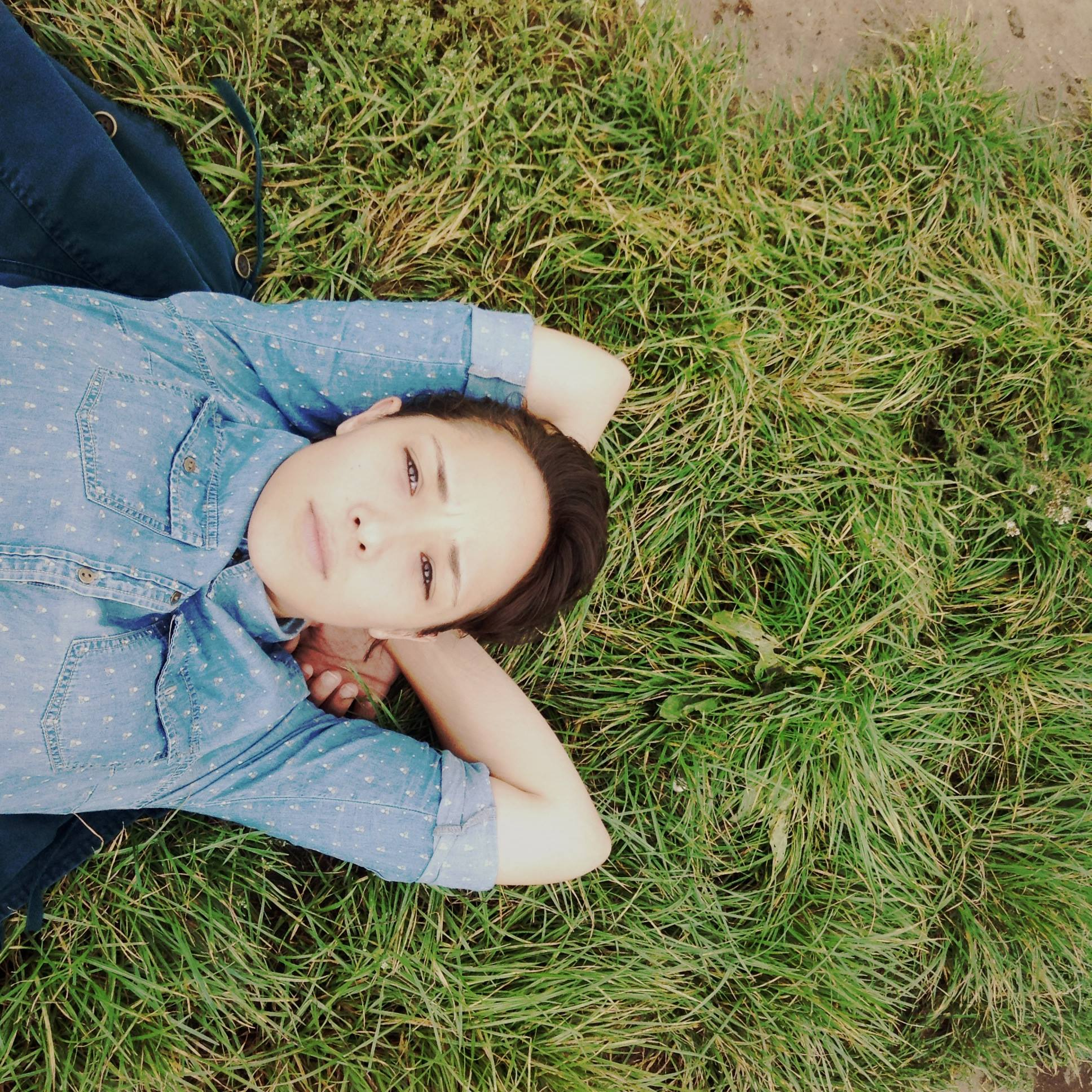 Ritty Tacsum photographer - color portrait of the photographer, lying on her back, on grass, looking at the camera