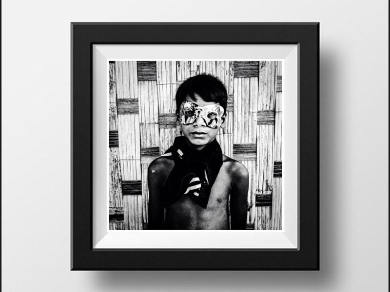 Black and white print boy wearing mardi gras mask 'Boy in Mask, Burma' © Jason Florio