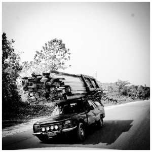 Black and white image heavily overloaded car 'Overload' Uganda © Jason Florio
