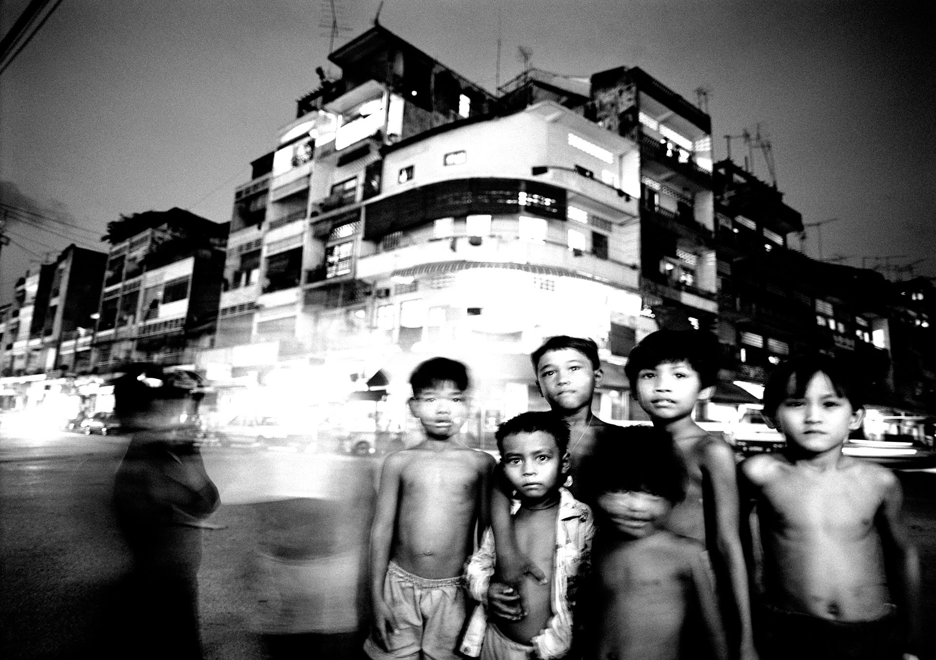ason Florio photography - Black & White image of a group of children, on a busy night time street, Cambodia