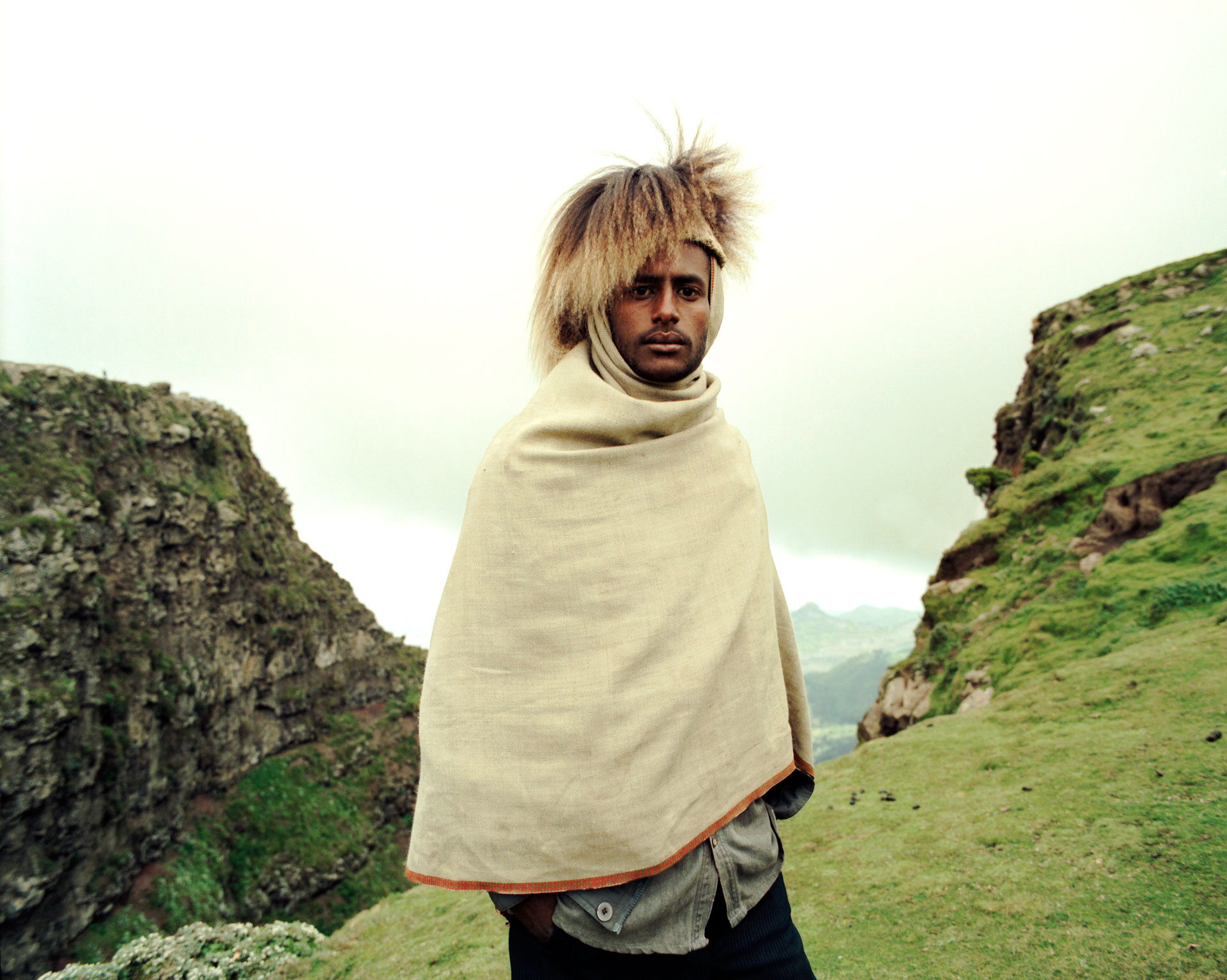 Jason Florio photography - color image a Ethiopian hill tribe man, in a baboon fur hat, on the edge of a cliff, in the Ethiopian Highlands