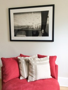 ©Chris Bartlett 'Feeding the Ponies'- black and white framed print, hanging on a wall, above a red arm chair