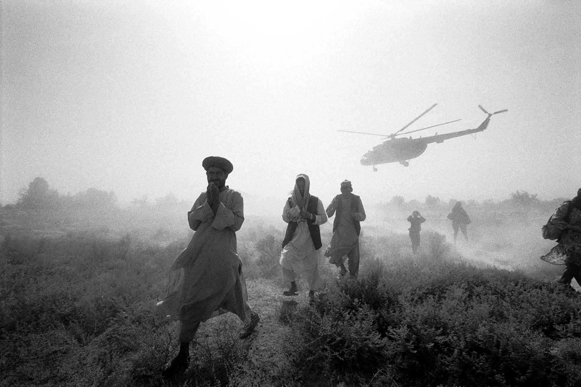 Jason Florio photography - black and white image of Afghani men walking away from a helicopter, which is taking off, in rural Afghanistan