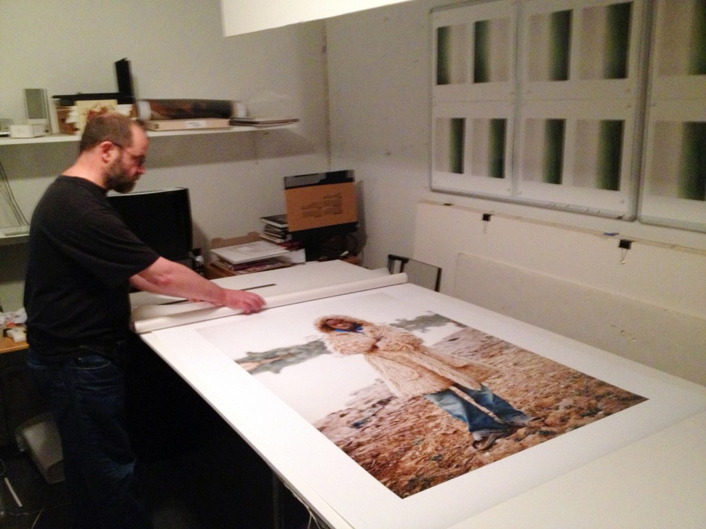 Pascal Prince, trims a large format print in his studio