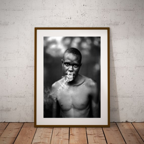 Black and white portrait of a young Gambian man blowing smoke from his nostrils, Gambia, W Africa 'ISMAILA SMOKING' © Jason Florio