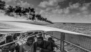 Magnum Photography Awards 2017-Jason Florio. Migrants onboard rescue boat with burning smuggler boat in foreground