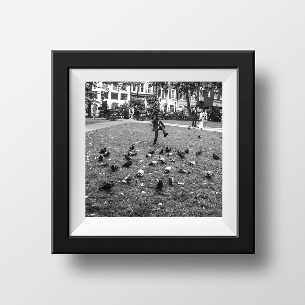 Gift inspiration: 'Romper Stomper' Soho Square, London © Jason Florio. Young black boy, in a suit, stamps the ground at pigeons on the park