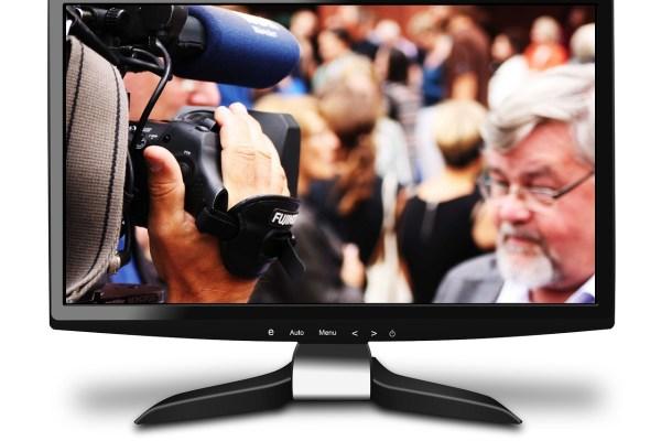Fernseher mit Politiker vor Mikrofon in Farbe