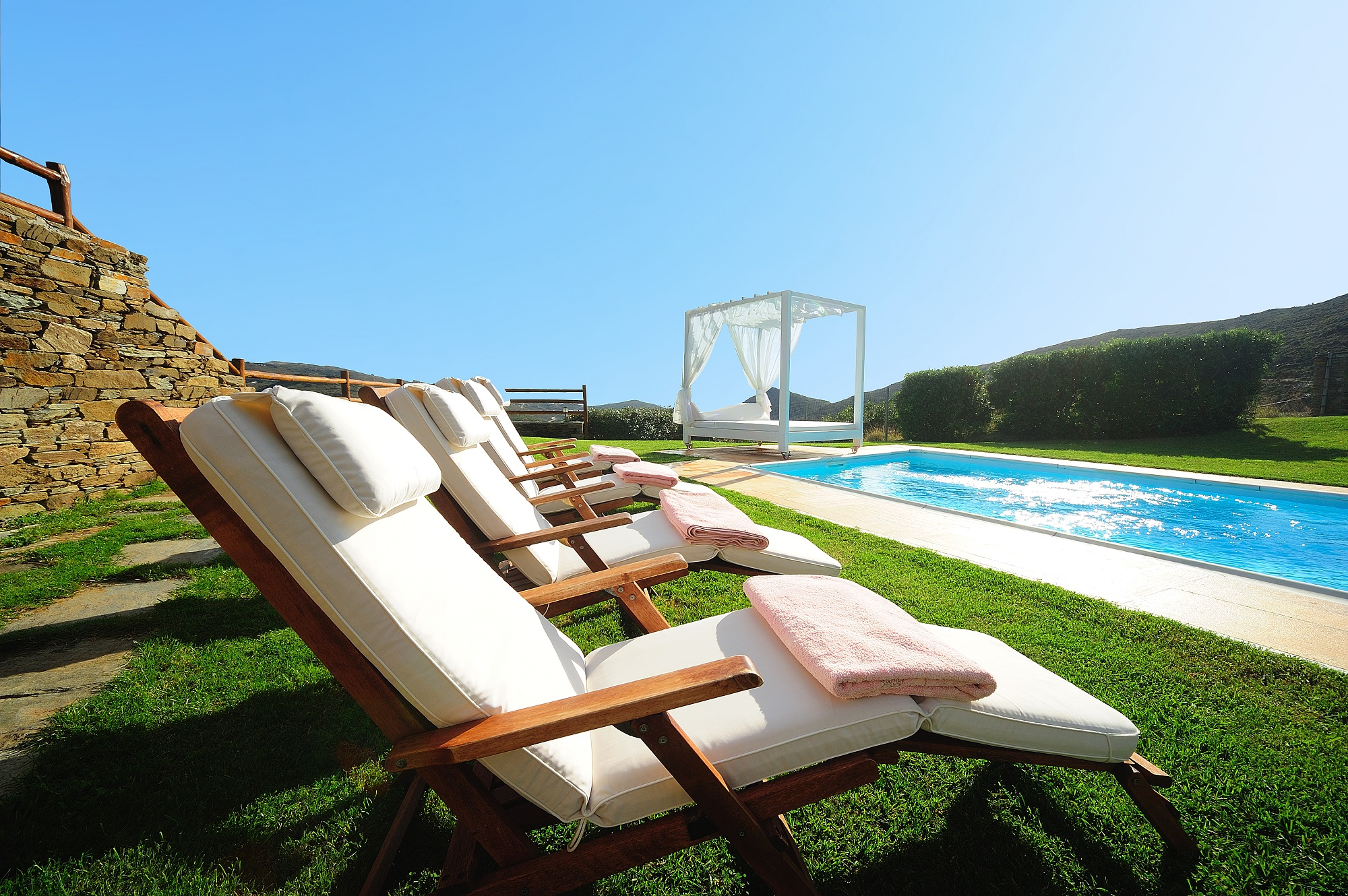 Sun lounges by the pool in the garden of Villa Helias