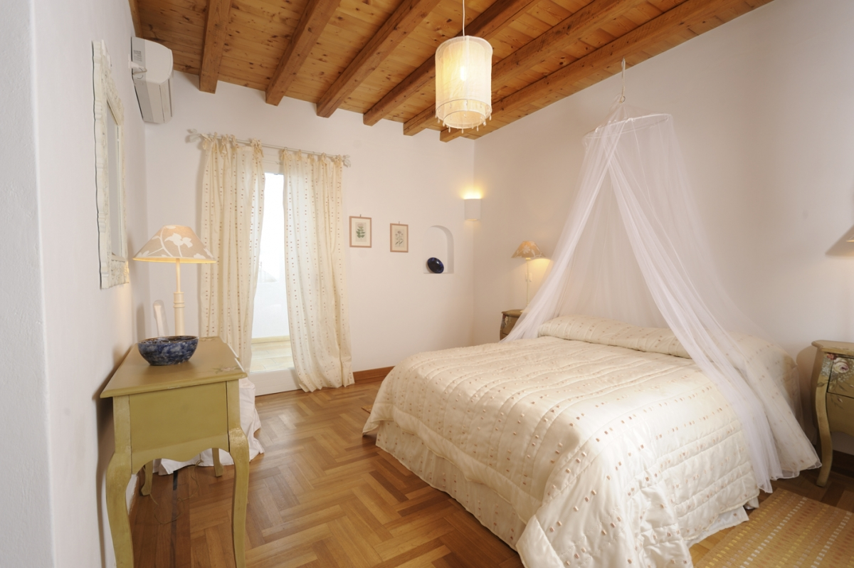 Large bedroom with double bed with mosquito net