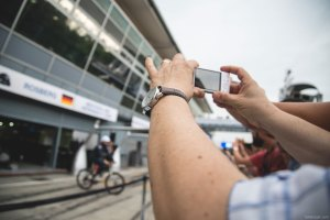 A fan takes a photo of Mercedes-Benz driver Nico Rosberg as he takes his bicycle out for a lap around the circuit.