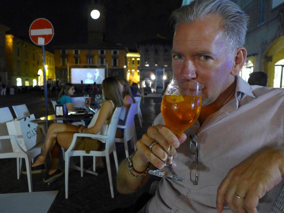 Erik drikker Spritz med utekinoen i bakgrunnen.