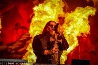 Ein Mann steht auf der Bühne und singt, im Hintergrund sind Flammen