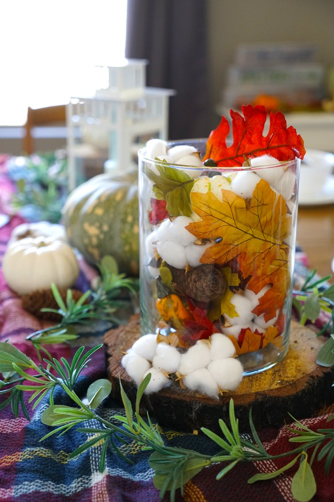 fall tablescape with plaid blanket, pumpkins, and cotton stems