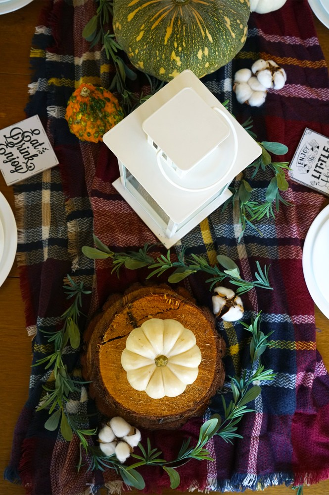 wood table with a plaid blanket and fall decor
