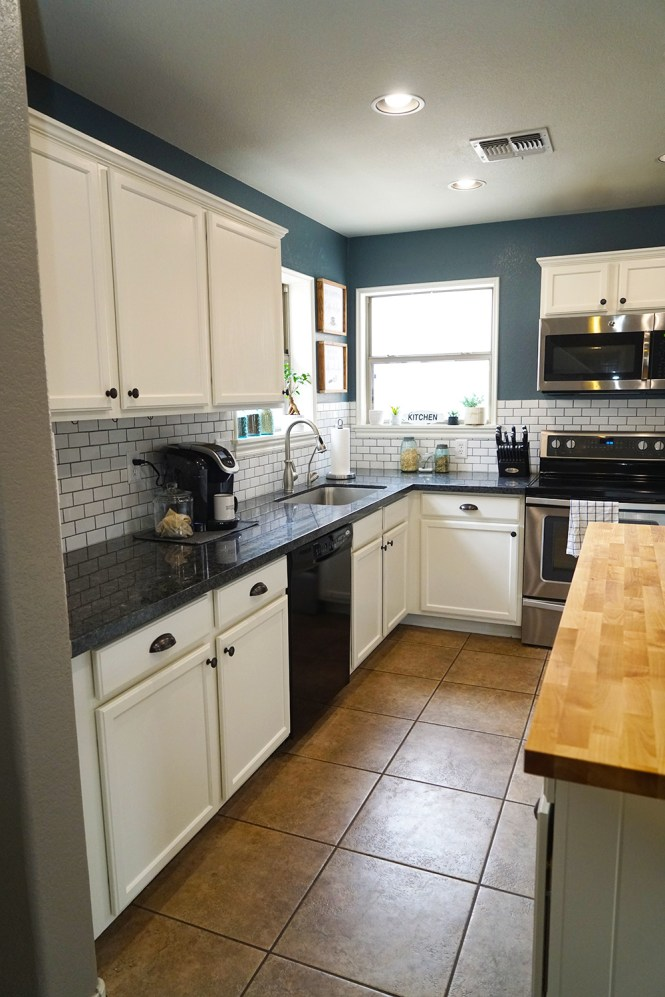 transformed kitchen with white cabinets, gray granite countertops, butcher block island, blue walls