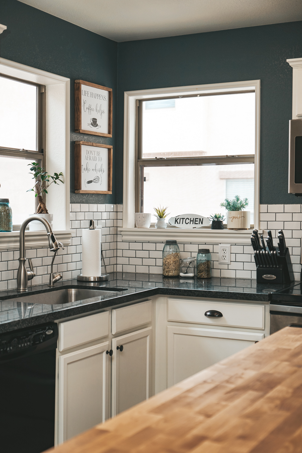 blue walls in a kitchen with subway tile, gray granite, and butcher block