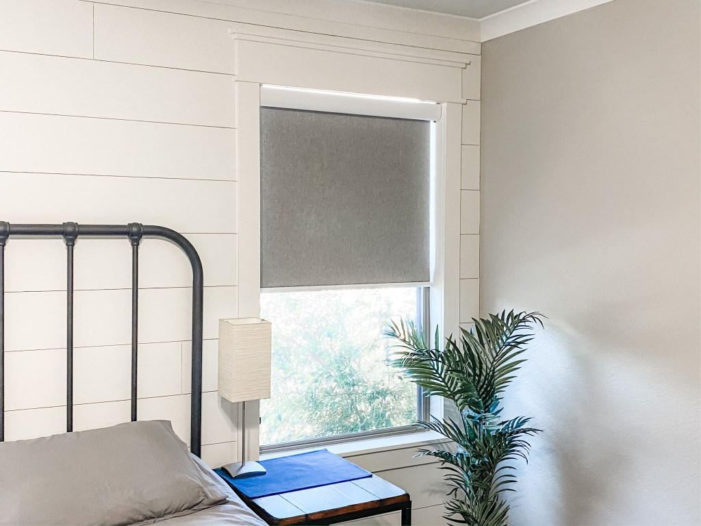 white shiplap in master bedroom with gray roller shade