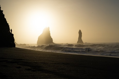 Sonnenaufgang am Reynisfjara Beach mit Mann auf den Felsen