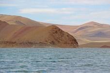 Hügelige Landschaft in der Mongolei vor einem See