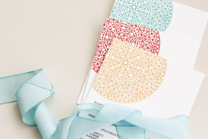 tiered invitation cards with silk aqua colored ribbon in teal, maroon and gold
