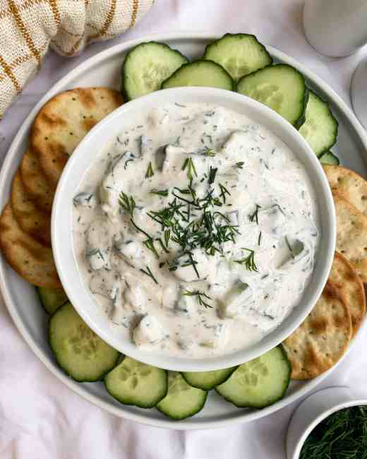 Healthy Five Minute Tzatziki in a bowl with cucumbers and crackers