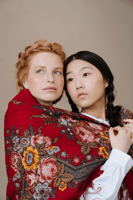 A red patterned shawl wrapped around two women who have their heads together