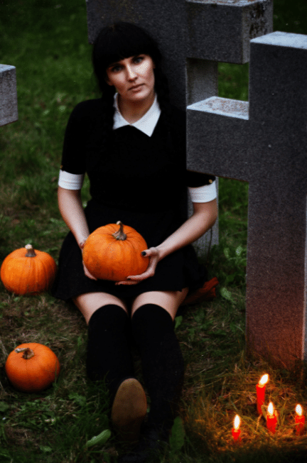 Woman dressed as Wednesday Addams holding a pumpkin