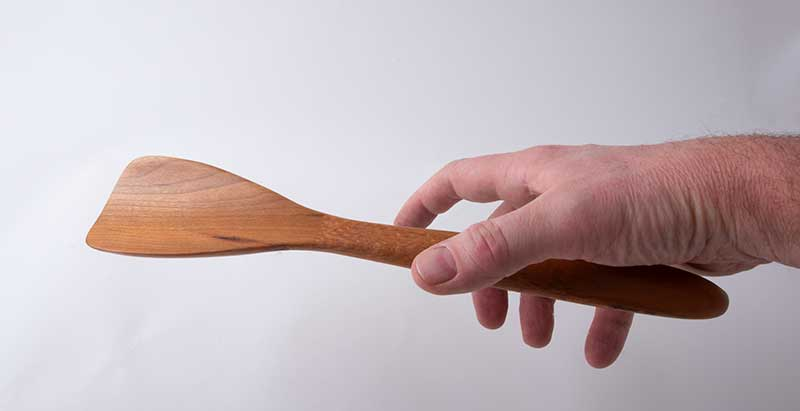 Hand reaching for a Blunt Spatula, in cherry