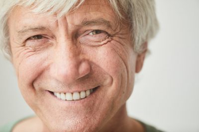 Close-up of happy senior man with white hair smiling at camera