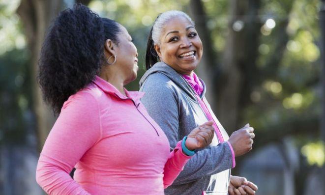 Women walking for exercise in park, smiling