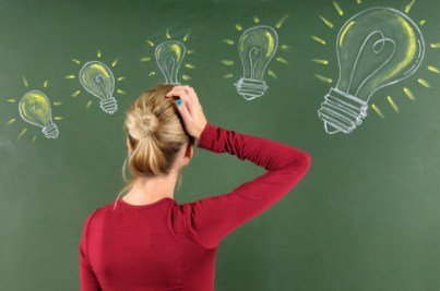 Woman scratching her head at light bulbs on chalkboard