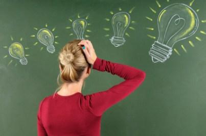 Woman scratching her head at light bulbs on chalkboard