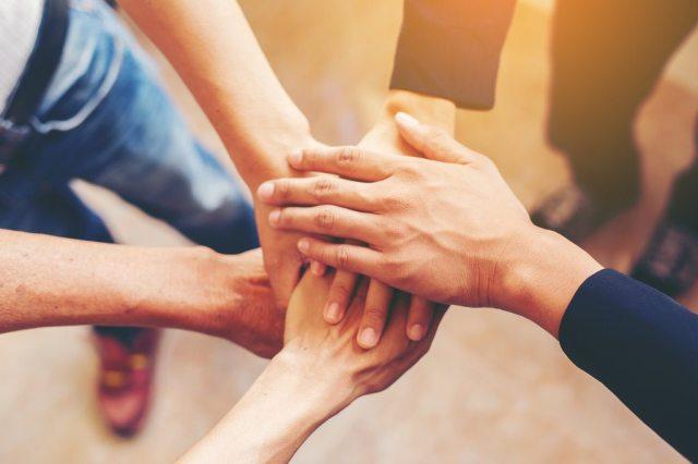 5 mains tendues qui se touchent pour symboliser une équipe